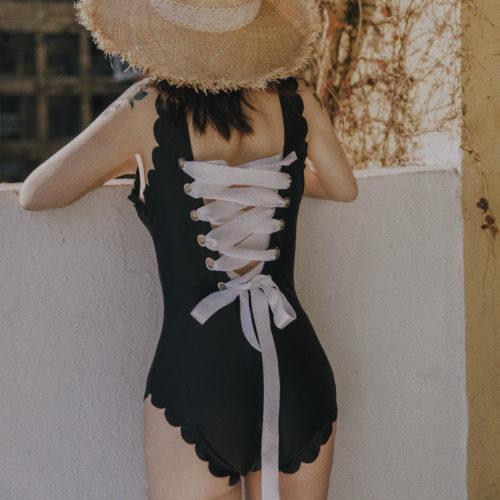 Слитный черный купальник с кружевными оборками и крупной белой шнуровкой на спине