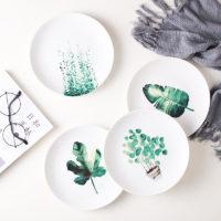 Керамические белые тарелки с зелеными растениями